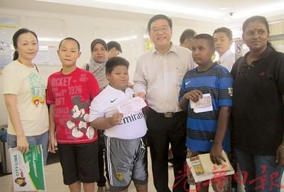 """黄汉伟(右3)与携带孩子前来领取""""2015年快乐学生计划""""款项的家长及学生合影。"""