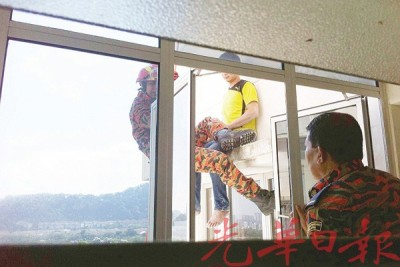 消拯员在公寓内外劝解坐在窗台边的青年。
