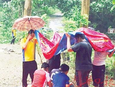 """华印裔及学为正为于雨中祷告的巫裔穆斯林同学撑起""""爱心伞""""。"""
