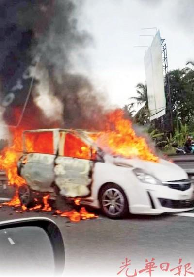 南北高速公路发生一辆轿车疑失控撞向大道分界堤后着火燃烧时的情形。
