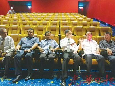 何强赞(右3)与末诺(右2)等人试坐电影院的座位。