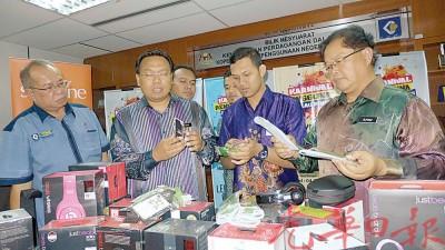纳瓦迪(左2)展示起获的各类耳机及手机品牌周边产品;右2苏海米。