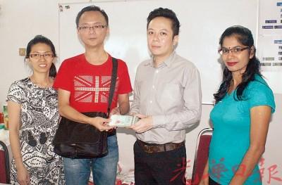 周先生(左2)移交义款给陈锦俊,左1是集邮群组会员林小姐,右1是中心助理Kuga。