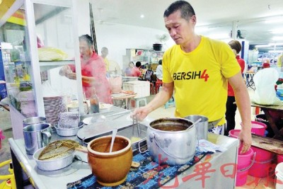 穿着黄色BERSIH4衣服的刘姓小贩,免费让身穿黄衣的顾客享用干捞面。