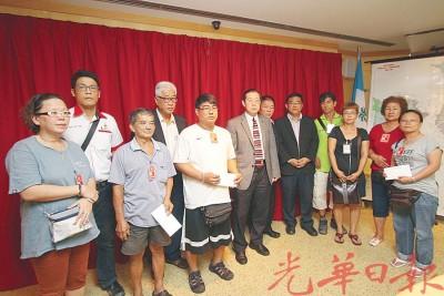 林冠英(左6)颁发援助金予3户受灾家庭。左4为彭文宝、左7为林峰成和黄汉伟。