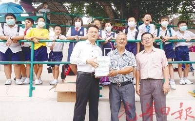 杨顺兴(左)移交口罩予公民二校,由李受廷(中)及林唐欣(右)代为接收。