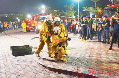 女性消防员参与演习,也群众示范开喉灭火。