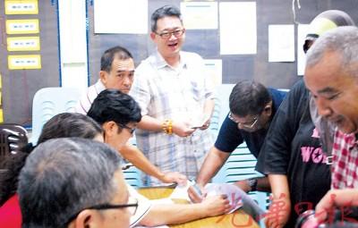 蔡通易(中)协助选民办理领取抚恤金手续。