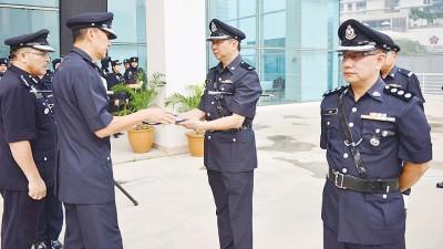 刘丰顺(左2)把褒扬奖状颁给两名华裔警官。