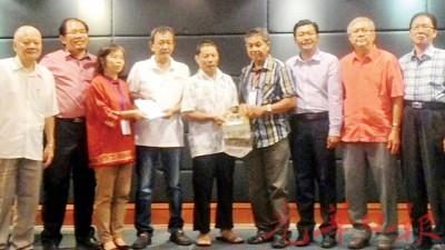 赖文强(左4)移交义款予林丽萍(左3),王德强(右4)回赠纪念锦旗,福气兴(着)搭领,由于吴顺财(左1)、签字理主席陈詠怀(右2)、程亚沥(右1)、黄伟益与郑来兴陪见证。