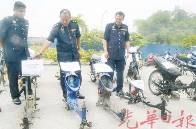 奥玛巴迪亚(中)在副警区主任拉祖安(右)等警官陪同下,向媒体展示起获的摩托车及零件。