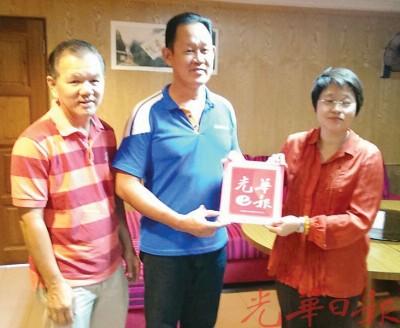 周美芬(右起)移交光华日报电子报予劳勿中华商会副会长莫家福及秘书叶官华。