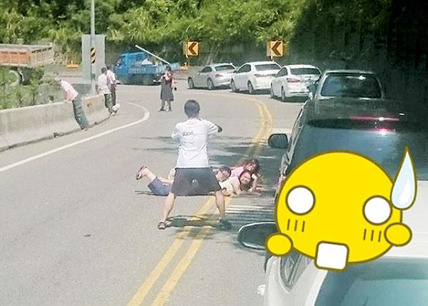 """名民众躺在路中央拍照,被网民炮轰""""脑残""""。"""