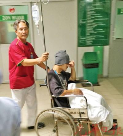 黄明志(坐者)在接受诊治后,坐在轮椅上由医护人员推入病房。