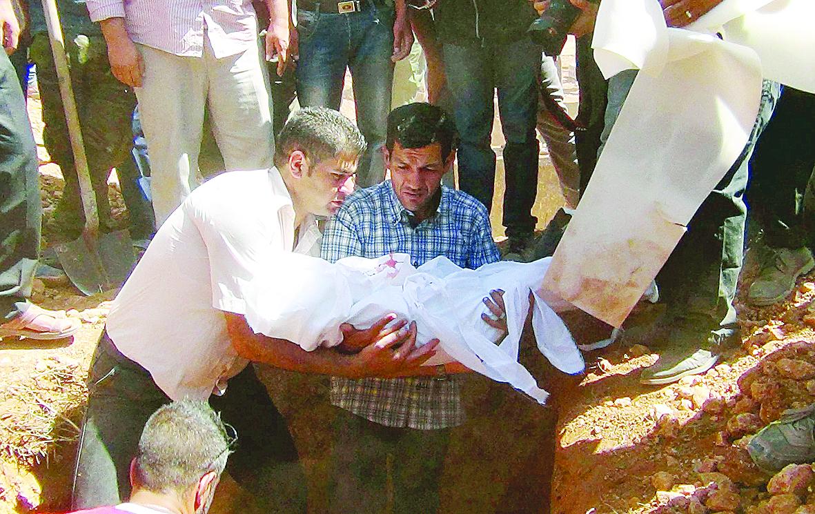 在家乡葬礼上,父亲科迪(中)一脸哀伤地抱着小难民艾兰的遗体。