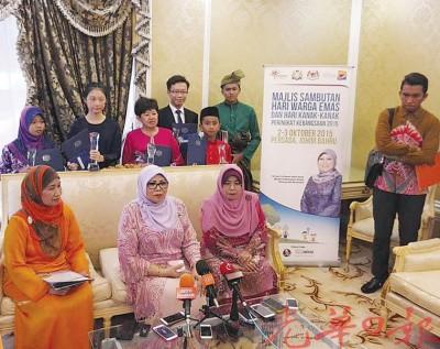 罗哈尼(中)在莎巴丽雅(左)及阿茜雅(右)的陪同下召开记者会。后排左起是妇女、家庭及社会发展奖项得主努鲁阿斯妮达、胡友芳、拿督陈莲花、邱齐轩、穆斯塔奇及穆基尔。