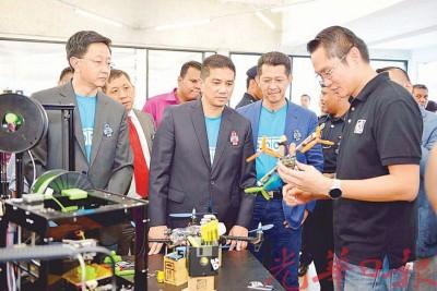阿兹敏阿里(中间者)与邓章钦(左起)在众人陪同下参观雪兰莪数位创意中心。