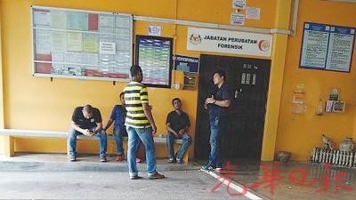為夫者(右二)在警方人員的陪同下在新山中央醫院太平間等待解剖報告。