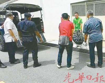 警方把死者遗体抬上卡车,准备送往槟城医院太平间解剖。