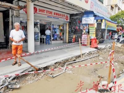 游客烦恼如何越过积水的马路。