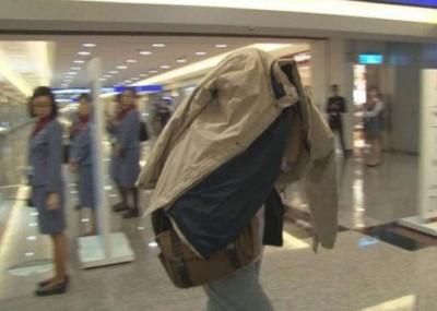 在班机上分娩的简姓妇人遭美遣返出境,她用外套盖住头部,不愿回应任何问题。