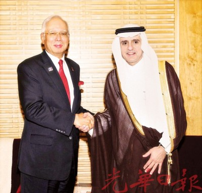 纳吉(左)向出席全球转型论坛的沙地阿拉伯外交部长阿迪尔握手问好。