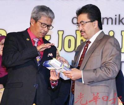 苏古(左)与佐哈里讨论财政预算案内容。