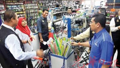吉打州贸消局执法组主任沙鲁丁(右)于一家钓鱼器材店员了解商品的标价。