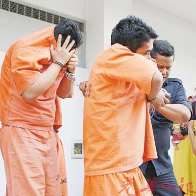 被告在被带出法庭扣留室时,以囚衣掩脸。