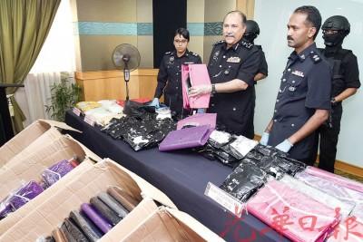 莫达(中)和立功警官在记者会上,展示起获的女性手提袋与毒品。