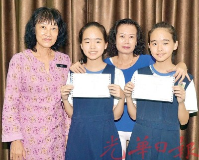 在小六评估试考获7A的港口路培华小学孪生姐妹王柔妍及王柔意欢欢喜喜的拿着成绩与母亲罗翠音及校长许馨云(左)合影。