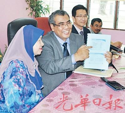 沙阿里奥斯曼展示今年槟州小六评估考试成绩报告,左是威北日落斗哇州议员拿督查哈啦,右2是杨国庆督学。