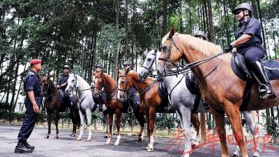 警方出动骑警队到吉隆坡会展中心维持东盟峰会会场的保安工作,带队警长查沙里(左)向队员汇报巡逻工作。