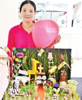 """谭巧帏成功获得冠军奖,欢喜地与其作品""""熊猫的婚礼""""合照。"""