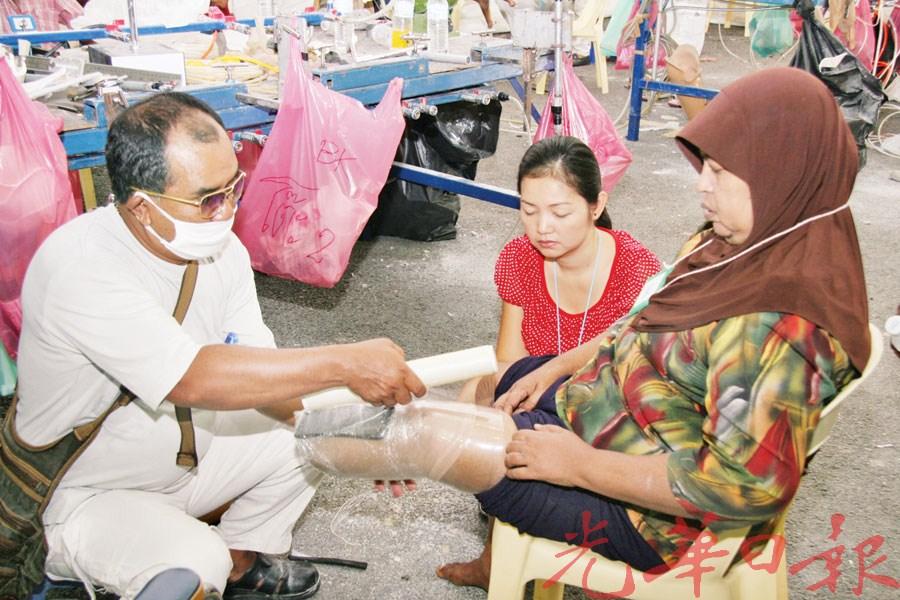 工作人员为求助者装置义肢。