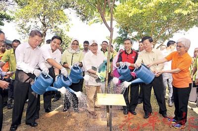 槟州元首敦阿都拉曼阿巴斯(中)带领众人浇洗树苗,左1起是林峰成、阿菲夫、麦慕娜、拉昔、曹观友及章瑛。