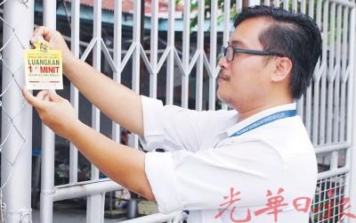 卫生局官员张贴宣传标签,号召居民每天花10分钟来清理住家环境。
