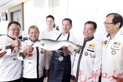 祝吉米(右3)与马克斯(左3)以新鲜三文鱼烹饪出一道道美食,左起为槟厨师代表李镇雄、齐垂兴、谢丕俐和陈保褣。