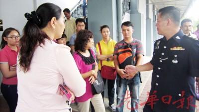 被告的丈夫郑翠平(右2)及被告的家属向警官查问案件进展。