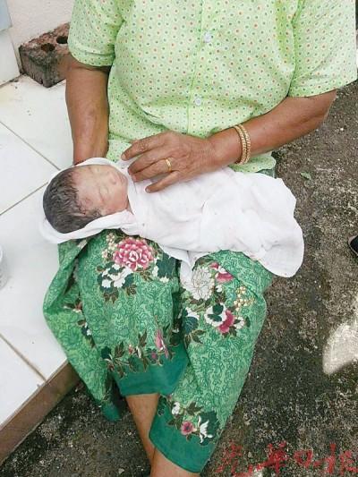 居民以毛巾包住全身发抖的男婴。