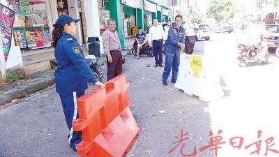 执法人员移走疑是作为非法霸占店屋前车位的路墩。