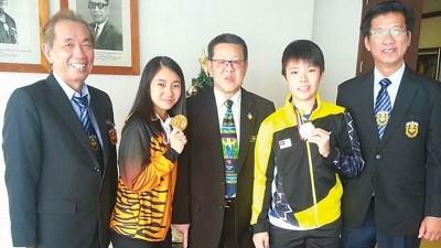 许庆吉(左)开心与两位世界冠军合影。左2为武术选手曾露奕及羽球选手吴堇溦(右2),体理会总监陈德安及槟羽总秘书准拿督梁建荣(右)陪同。
