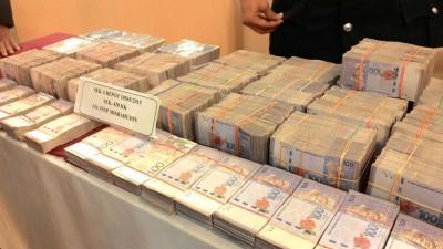 警方在记者会上向媒体展示行动中所起获的270万令吉现款。