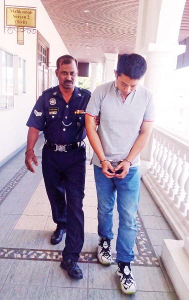被告陈国威(译音)低头回避媒体镜头。