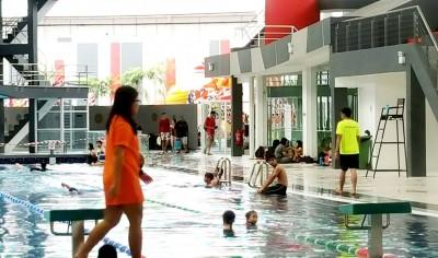 游泳中心内人潮拥挤,泳池旁坐着许多人等候下泳池畅游。