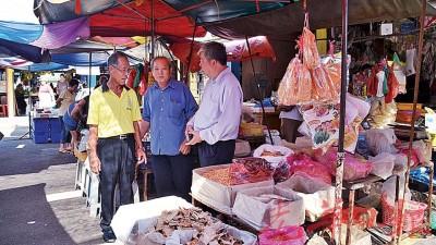 (右起)陈宗兴、陈宥光及余万祥巡视探讨店面小贩延伸摆卖情况。