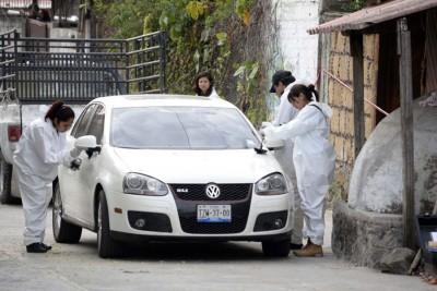警方鉴证人员检查泊在莫塔寓所外的一部汽车。