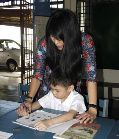 老师握着俊艺的小手,1对1的细心教他写字。