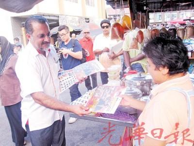 佳日星(左)前往关丹路巴刹分发2016年日历给民众。