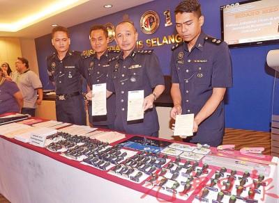 沙克里(右2)与立功警官星期五在记者会,出示搜到的各伪造假病假单的物件。